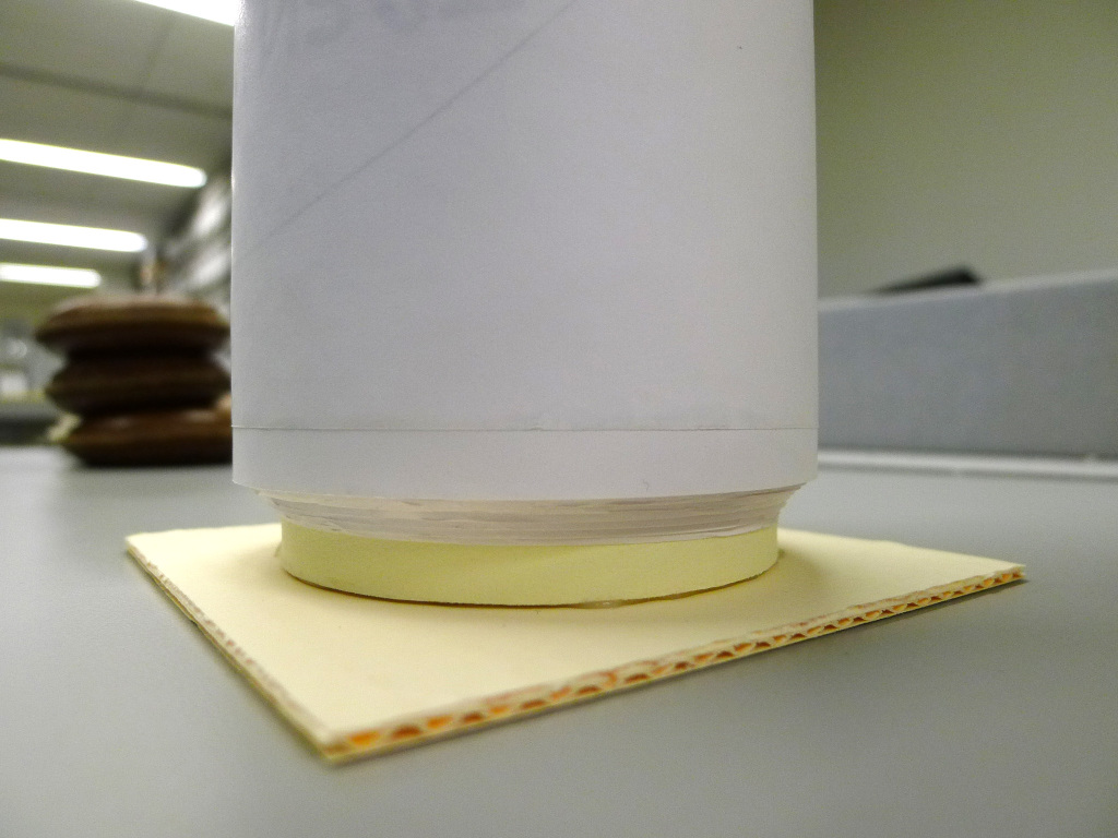 IMAGE 2: Bottom of archival core, showing attachment of corrugated board foot with electrical-grade hot-melt adhesive, and bottom edge of rolled drawings.