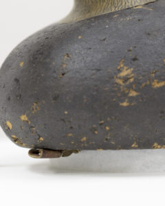 "Fig. 9. Detail of black duck decoy on mount; note how the mount sits within the perimeter of the base of the duck.  Charles ""Shang"" Wheeler, Black Duck Decoy, unknown date. Cork, wood, paint, glass, metal and leather, 16.19 X 18.73 X 45.09 cm (overall). Collection of Shelburne Museum, gift of Mrs. Howard Newton. 1969-77"