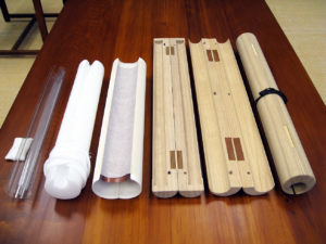 Fig. 5 - These modern preservation rollers are made of acid-free materials (pictured on the left) or traditional wood (pictured on the right). From left are conservation rollers made of: Mylar; Ethafoam with Stockinette; neutral paper tube with Japanese paper sling and scavenger insert; paulownia wood from Japan with closed ends; paulownia wood with open ends; and locally harvested paulownia wood for a roller made in the United States.