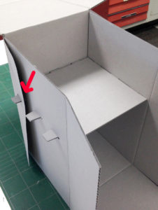 Fig. 14. Shelf dry fit into box with tabs cut into the back wall and two sides, including the side flaps (red arrow).