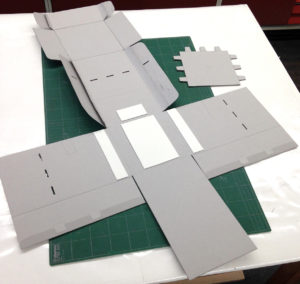 Fig. 15. Flat box with all necessary cuts, creases, and magnets, ready for final assembly, with interior shelf in upper right hand corner.