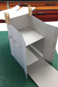 Fig. 16. Assembling the box by first gluing the back wall flaps to the right and left sides with the shelf in place.