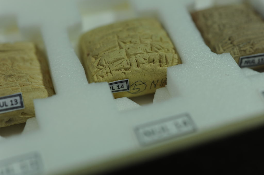 We mark objects and housings in several ways.  The old, inconsistent, pencil inscriptions on these cuneiform tablets were superseded by paper labels with the ownership and call number information.