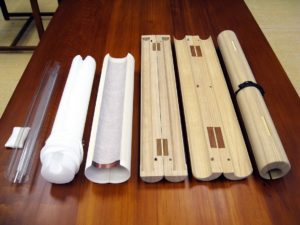 Figure 5. These modern preservation rollers are made of acid-free materials (left) or traditional Paulownia wood for roller clamps (right). From the left are conservation rollers made of mylar; Ethafoam with Stockinet; neutral paper tube with Japanese paper sling and scavenger insert; Paulownia wood roller clamp from Japan with closed ends; Paulownia wood with open ends; and locally harvested Paulownia wood for a roller clamp made in the United States.